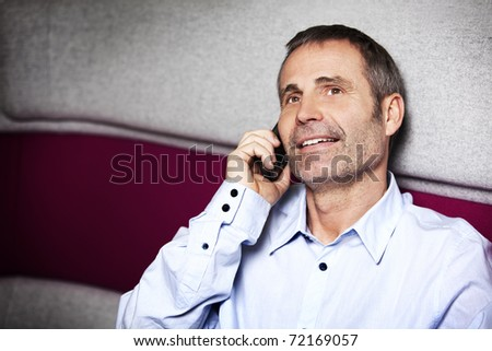 Friendly senir businessman in blue shirt sitting on sofa and talking on cell phone. - stock photo