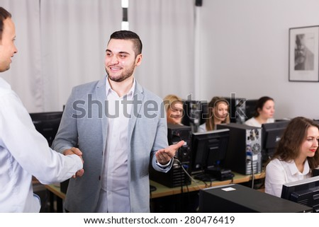 Friendly smiling boss greeting new colleague at office - stock photo