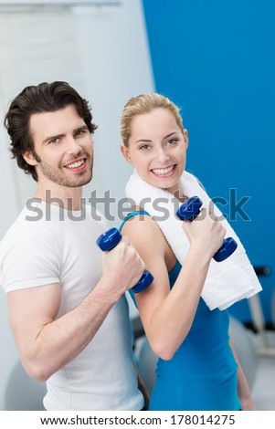 Friendly smiling couple working out with dumbbells in the gym standing close together training in unison flexing their arms to tone their muscles - stock photo