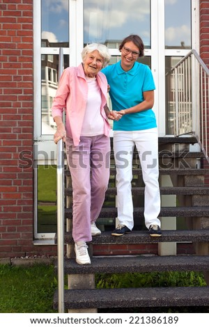 Friendly smiling female carer helping a senior lady walk down a flight of exterior wooden steps holding her by the hand for support. - stock photo