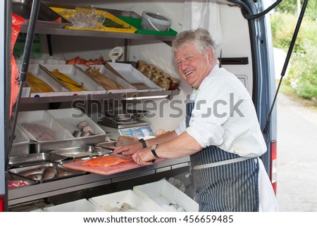 Friendly smiling man serving fresh fish from a mobile van.  A sole trader in Wales.