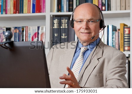 Friendly smiling man with headphones, notebook and webcam, telephoning via skype, copy space - stock photo