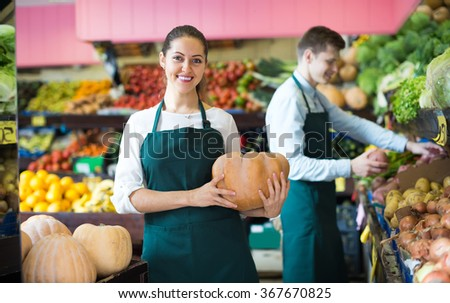 Friendly smiling market workers offering for retail large squash