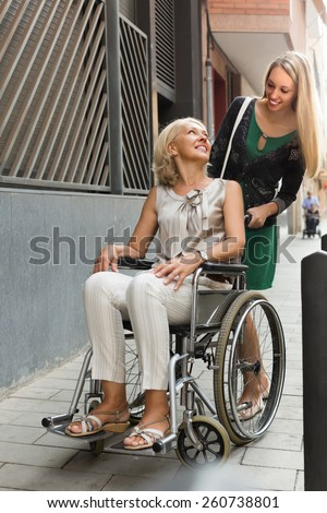 Friendly smiling social worker and disabled mature woman on chair at stroll - stock photo