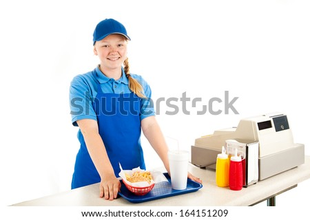 Friendly, smiling teenage cashier serving fast food in a restaurant.  Isolated on white.   - stock photo