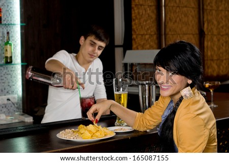 Friendly smiling woman sitting at a bar drinking a pint of beer and eating snacks turning to look at the camera with a smile as the barman works in the background - stock photo