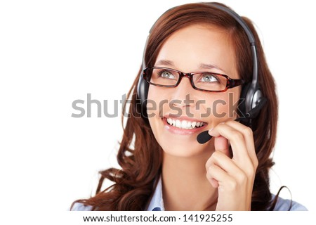 Friendly smiling woman wearing a headset and glasses as she works at a call centre or client services help desk, isolated on white - stock photo