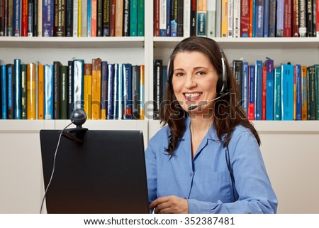 Friendly smiling woman with computer, webcam and headphone at a callcenter, hotline or helpdesk - stock photo