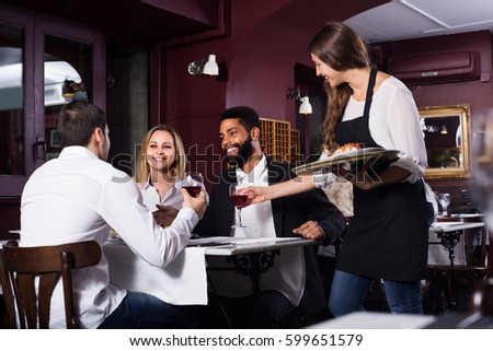 Friendly smiling young waitress serving meal for guests at table in restaurant