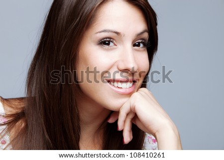 friendly smiling young woman portrait hand lean on chin,  studio shot