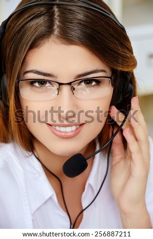 Friendly smiling young woman surrort phone operator at her workplace in the office. Headset. Customer service. - stock photo