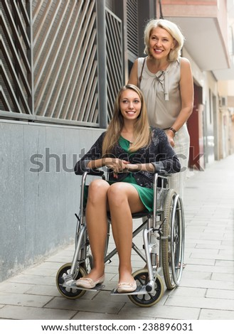 Friendly social worker and disabled girl on chair at stroll. Focus on girl - stock photo