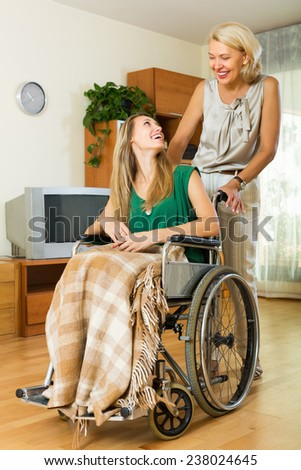 Friendly social worker and smiling disabled girl on chair returning home - stock photo