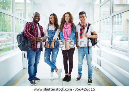 Friendly students in casual-wear standing in college corridor - stock photo