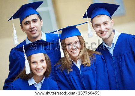 Friendly students in graduation gowns looking at camera - stock photo