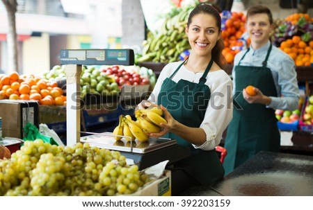 Friendly stuff in aprons selling sweet bananas at marketplace - stock photo