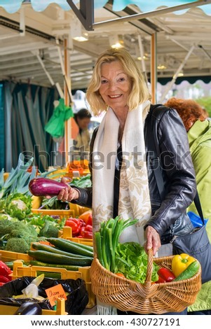 Friendly stylish middle-aged blond woman shopping for fresh fruit and vegetables on an open-air market stall carrying a wicker basket with her selection - stock photo