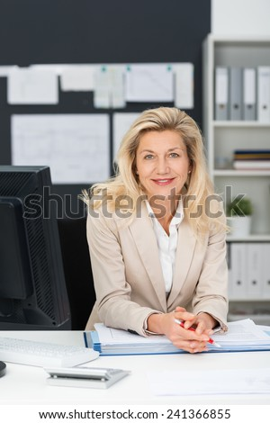 Friendly stylish middle-aged businesswoman leaning on a folder on her desk in the office smiling at the camera - stock photo