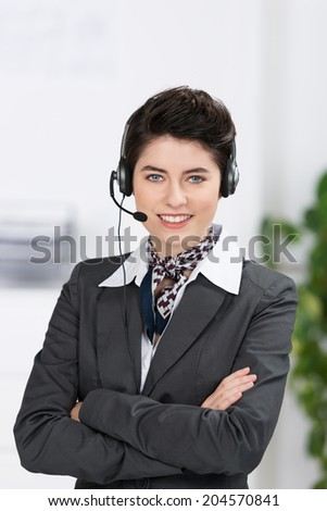 Friendly stylish receptionist or customer services officer in an elegant uniform and headset standing with folded arms smiling at the camera - stock photo