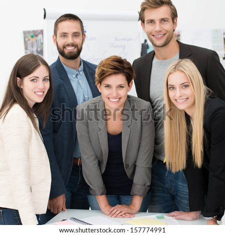 Friendly successful business team of multiethnic young executives standing together posing for the camera and smiling - stock photo