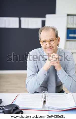 Friendly successful middle-aged businessman wearing glasses sitting at his desk with paperwork smiling at the camera - stock photo