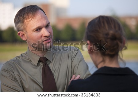 friendly talk between a businessman and woman on the street - stock photo
