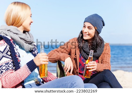 Friendly talk. Two beautiful young women drinking beer and talking to each other while sitting on the beach together - stock photo