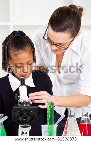friendly teacher helping primary schoolgirl in science class - stock photo