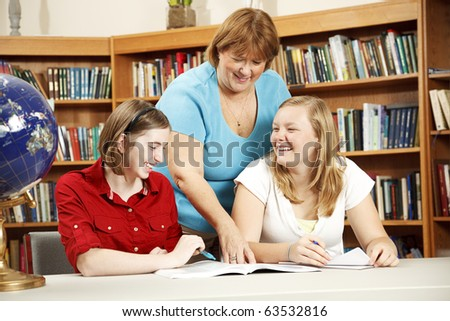 Friendly teacher or librarian helping teenage students in the library.
