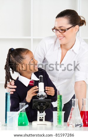 friendly teacher talking to elementary student in science class - stock photo