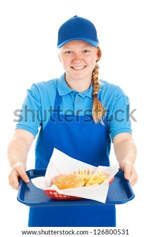 Friendly teenage fast food worker serving a burger and fries meal with a smile.  Isolated on white. - stock photo