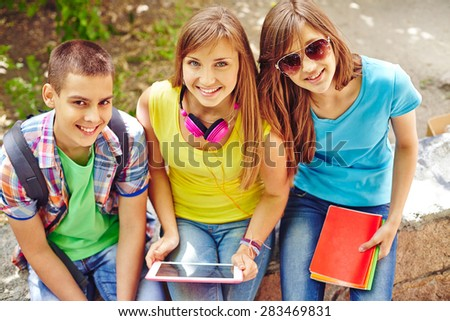 Friendly teenagers sitting in park and looking at camera