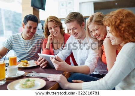 Friendly teens with touchpad spending leisure in cafe