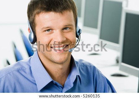 Friendly telephone operator smiling during a telephone conversation - stock photo