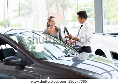 friendly vehicle dealer showing young woman new car - stock photo