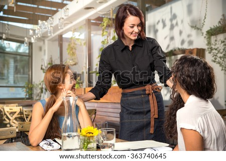 Friendly waiter server laughing smiling having fun with customer patron pretty modern - stock photo