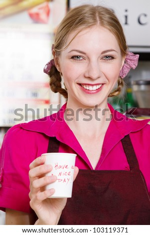 Friendly waitress making coffee at coffee machine - stock photo