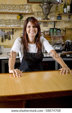 Friendly waitress standing behind counter in restaurant - stock photo