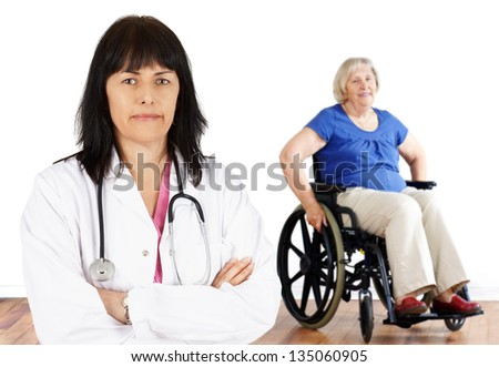 Friendly woman doctor looking at camera with handicap senior in wheelchair in the back - stock photo