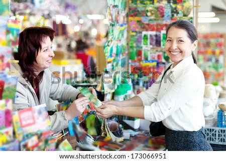 friendly woman selling seeds to mature buyer in store for gardeners - stock photo