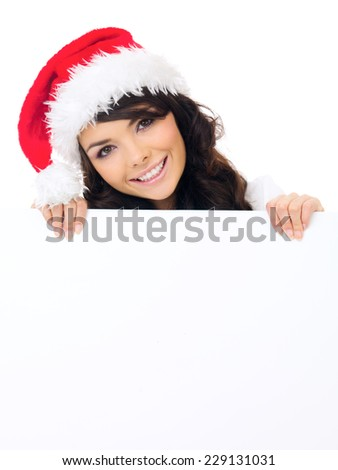 Friendly woman wearing a red Santa hat with a blank Christmas sign in her hands with copyspace for your text or seasonal greeting - stock photo
