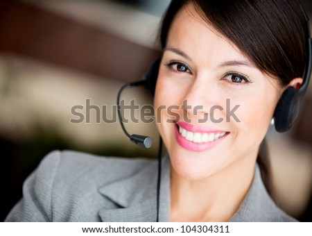 Friendly woman working at a call center smiling - stock photo