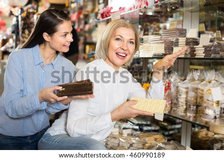 Friendly women buying dark and white chocolate bars and smiling. Selective focus
