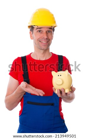 friendly worker with helmet is pointing of a piggy bank  - stock photo