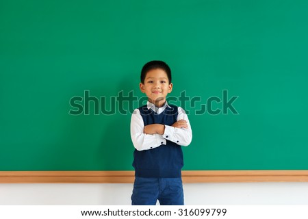 Friendly young asian school boy with his arms folded / photo of teen school Chinese boy, creative concept with Back to school theme - stock photo