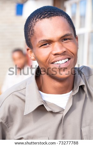 Friendly young black african male close up with another boy in the back. - stock photo