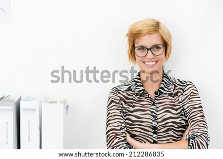 Friendly young blond businesswoman wearing glasses with a warm smile standing looking at the camera with folded arms in the office with copyspace - stock photo