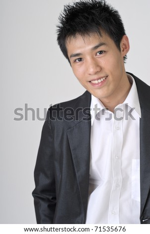 Friendly young business man of Asian, closeup portrait on gray background. - stock photo