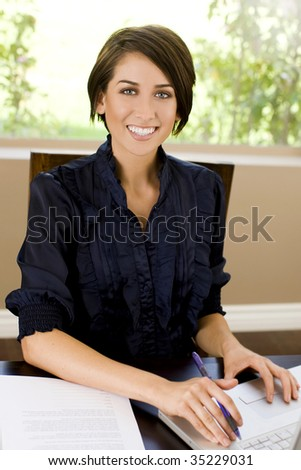 Friendly young business woman at her desk - stock photo