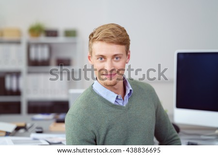 Friendly young businessman smiling at the camera as he turns in his chair at the office while working at a desktop computer - stock photo